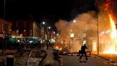 A shop and police car burn as riot police try to contain a large group of people on a main road in Tottenham, north London on August 6, 2011 (AFP Photo / Leon Neal)