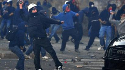 Masked demonstrators throw projectiles to anti-riot police squad during a demonstration, in Rome on October 15, 2011 (AFP Photo / Alberto Pizzoli)