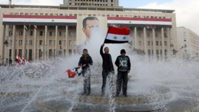 Syrian government supporters wave national flags they stand in a fountain in front of a portrait of President Bashar al-Assad during a pro-regime rally in Damascus (AFP Photo / LOUAI BESHARA)