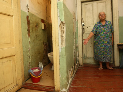 An elderly woman demonstrates the condition of her apartment in a dilapidated building. (RIA Novosti/Alexandr Kryazhev)