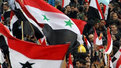 Syrians wave national flags as they rally in central Damascus on November 16, 2011. (AFP Photo/Louai Beshara )