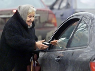 An elderly beggar receives money from the driver of a foreign car in downtown Moscow (AFP Photo / Yuri Kadobnov)