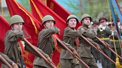 Soldiers in WWII-era uniforms bearing Soviet flags (Photo by Alexey Novikov)