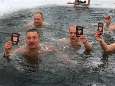 "Members of the ""Polar Bear"" sports club show their passports as they swim in a hole cut in the frozen river Ob before voting in the parliamentary election in Barnaul, the capital of Altai region December 4, 2011. (REUTERS/Andrei Kasprishin)"