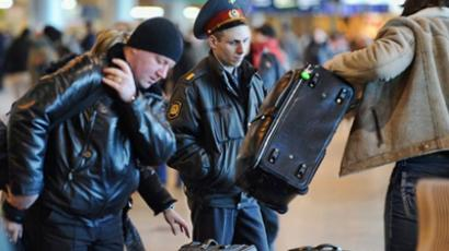 Moscow: A Russian policeman looks at passengers arriving with their luggage at a security checkpoint at Domodedovo airport outside Moscow, on January 25, 2011. (AFP Photo / Alexander Nemenov)
