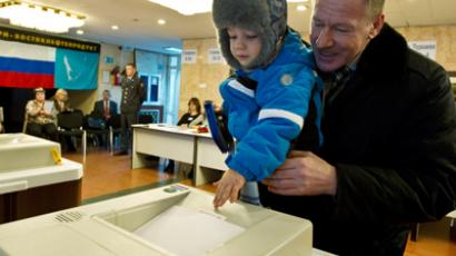 Man with a child drops a ballot into an automated ballot box to vote at polling station №332 in Yuzhno-Sakhalinsk (AFP Photo / Sergey Krasnouhov)