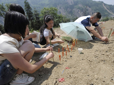 Quake survivors pray at the tombs of their loved ones (AFP photo / Liu Jin)