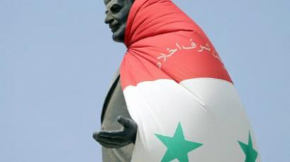 Syria: A national flag hangs on a statue of Syria's late president Hafez al-Assad at the entrance of the flashpoint city of Homs, 160 kms northeast of Damascus, on August 30, 2011. (AFP Photo/Joseph Eid)