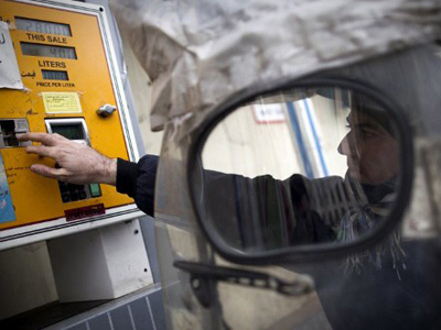An Iranian man inserts his fuel smart card in the machine to fill his motorcycle at a petrol station in Tehran (AFP Photo / Behrouz Mehr)