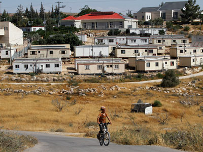 A young Jewish settler rides a bicycle in front of the West Bank settlement of Susiya (Reuters / Baz Ratner)