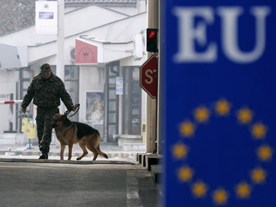 A Bulgarian border policeman leads his dog at the border between Bulgaria and Greece (Reuters / Nikolay Doychinov)