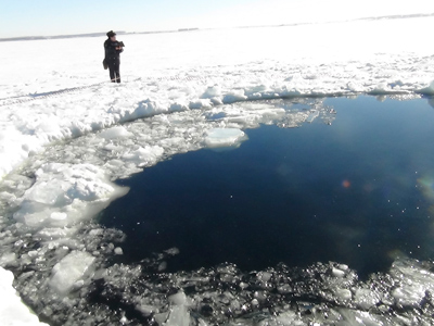 A Russian policeman works near an ice hole, said by the Interior Ministry department for Chelyabinsk region to be the point of impact of a meteor seen earlier in the Urals region, at lake Chebarkul some 80 kilometers (50 miles) west of Chelyabinsk February 15, 2013 (Reuters / Chelyabinsk region Interior Ministry)