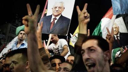 Palestinians gather in the West Bank city of Ramallah to watch a wide screen relaying live footage of a historic bid for statehood by Palestinian Authority President Mahmud Abbas (portraits) at the United Nations General Assembly in New York on September 23, 2011 (AFP Photo / ALESSIO ROMENZI)