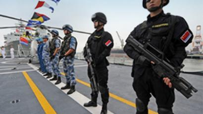Philippines, Manila: People's Liberation Army (PLA) Navy special force members stand on the desk of China's Task Force 525 flagship missile frigate Ma'Anshan which saw action in Somalia against pirates as the ship anchors at the international port in Manila on A pril 13, 2010. (AFP Photo /Ted Alijeb)