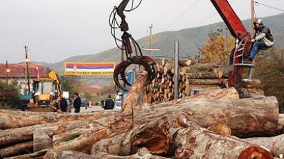 A Kosovo Serb lifts wooden logs from a barricade in Zupce, Nothern Kosovo (AFP Photo / STR)