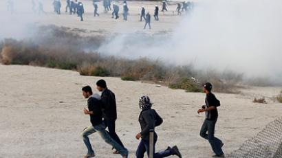 Anti-government protesters run as tear gas is fired by riot police after protesters broke through barriers to advance towards Farooq Junction formerly known as Pearl Square in Budaiya west of Manama, February 13, 2012  (Reuters / Hamad I Mohammed)