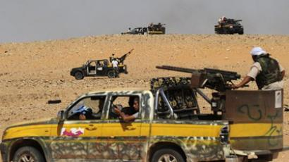 Libyan National Transitional Council (NTC) fighters drive their trucks, with mounted artillery, over the hills leading to the desert town of Wadi Bey on September 15, 2011, as a convoy of forces loyal to Libya's new rulers came under heavy fire while advancing on Moamer Kadhafi's hometown of Sirte in a bid to take one of his final pockets of resistance (AFP Photo / FRANCISCO LEONG)