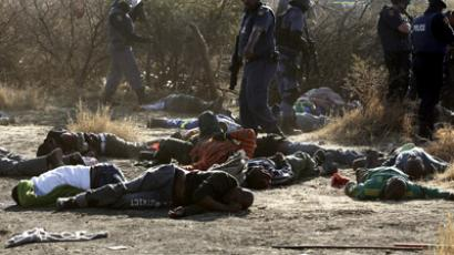 A policeman gestures in front of some of the dead miners after they were shot outside a South African mine in Rustenburg, 100 km (62 miles) northwest of Johannesburg, August 16, 2012. (Reuters/Siphiwe Sibeko)