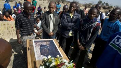 Mineworkers pray on August 31, 2012 over the coffin containing the body of Mpuzeni Ngxande, one of the 34 striking miners that were killed by police.(AFP Photo / Rodger Bosch)