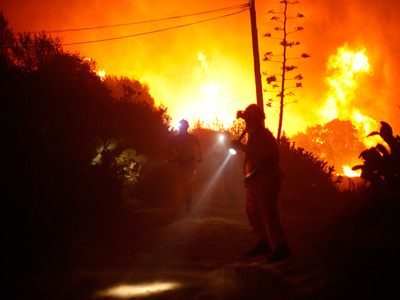 Members of the Civil Protection service run as they look for people inside a chalet during a general evacuation at a residential area, as a forest fire rages in Elviria, near Malaga, southern Spain, early August 31, 2012 (Reuters / Jon Nazca)