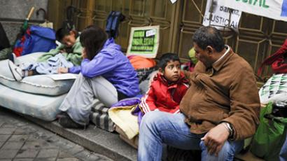 People sit in front of banners and placards displayed by evicted people outside a branch of Caja Madrid, part of the Bankia group bailed out by the Spanish state, during a protest against evictions on the Plaza Celenque in Madrid on October 25, 2012. (AFP Photo / Pedro Armestre)