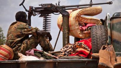 A SPLA (South Sudan People's Liberation Army) soldier sits next to a machine gun on a vehicle outside a SAF compound in Heglig, on April 17, 2012 (AFP Photo / Adriane O'Hanesian)