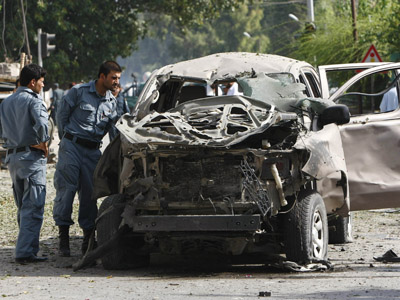 Afghan policemen inspect a vehicle hit by a bomb blast in Jalalabad province August 13, 2012. (Reuters/Parwiz)