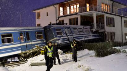 Policemen stand in front of a local train that derailed into a residential building in Saltsjoebaden, Sweden, on January 15, 2013.(AFP Photo / Jonas Ekstromer)
