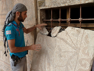 A Syrian rebel fighter inspects a mosaic piece at the Alma Arra museum in Maarat al-Numan, in Syria's northwestern Idlib province, on October 11, 2012.  (AFP Photo / Herve Bar)