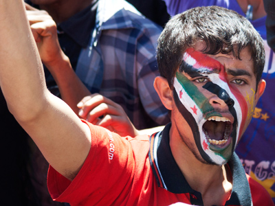 An anti-government protester shouts slogans with the colours of the national flag of Yemen and Syria painted on his face during a rally against the immunity of Yemen's outgoing president Ali Abdullah Saleh in Sanaa January 23, 2012 (Reuters / Mohamed al-Sayaghi)
