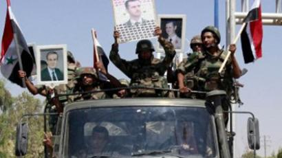Syrian soldiers hold pictures of Syrian President Bashar al-Assad and his late father, former president Hafez al-Assad, (L) as they leave the eastern city of Deir Zor following a 10-day military operation on August 16, 2011 (AFP PHOTO / STR)