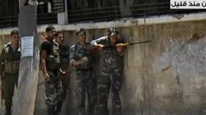"Syrian security forces taking position during armed clashes with gunmen who the TV called ""terrorists"" (unseen) in the Al-Midan district of Damascus on July 18, 2012 (AFP Photo / HO / Syrian TV)"