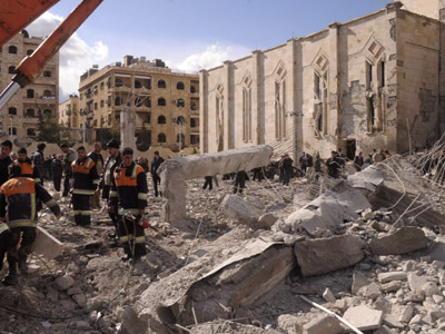 Syrian workers inspect the site of an explosion outside a military security building, one of two sites of bomb blasts in Syria's northern city of Aleppo. (Reuters / Sana Sana)