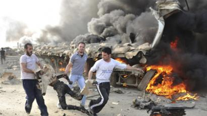 People run carrying a burnt body at the site of an explosion in Damascus May 10, 2012. (Reuters / Sana)