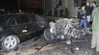 People stand near a damaged car and debris after explosions went off at the main gate of the Syrian Interior Ministry in Damascus December 12, 2012, in this handout photograph released by Syria's national news agency SANA (Reuters / SANA)
