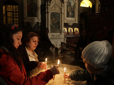 Syrian Christians light candles during a service at the al-Zaytoun Church in Bab Touma Square in Damascus, on December 13 , 2011 in support of Syrian President Bashar Assad and in memory of those killed in the ongoing unrest in the country (AFP Photo/Louai Beshara)