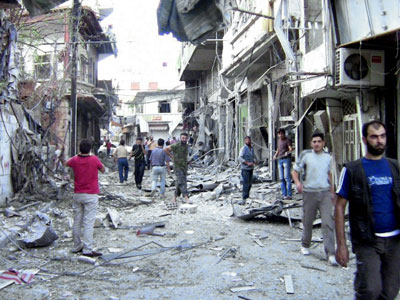 Syrian opposition's Shaam News Network shows Syrian men inspecting the damage allegedly caused by shelling by regime forces of a shopping district in Zabadani, 40 km northwest of the capital Damascus, in the Rif Damascus province on August 8, 2012. (AFP Photo / Shaam News Network)