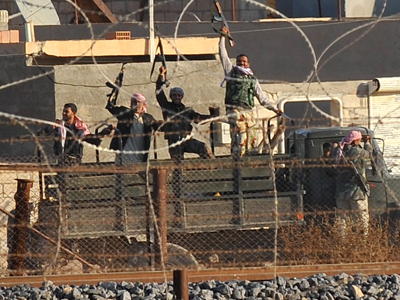Photo taken from the Turkish border town of Ceylanpinar shows Syrian oppsosition fighters celebrating on the strategic Syrian border town of Ras al-Ain, on November 14, 2012 (AFP Photo / Bulent Kilic)