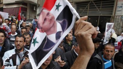 A member of the Druze community holds up a Syrian flag with a picture of Syria's President Bashar al-Assad. (Reuters / Baz Ratner)