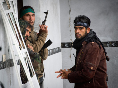 Rebel soldiers stands guard inside a building in the northern Syrian city Aleppo  (AFP Photo / Odd Andersen)