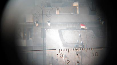 A view seen though a sniper's scope held for the photographer by a Free Syrian Army fighter shows a Syrian flag fluttering in an area controlled by forces loyal to Syria's President Bashar al-Assad near Aleppo's historical citadel November 28, 2012 (Reuters / Saad Al-Jabri)