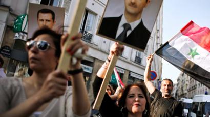 Supporters of the Syrian President's regime hold portraits of Syrian President Bashar al-Assad as they demonstrate in front of the Syrian cultural center (AFP Photo)