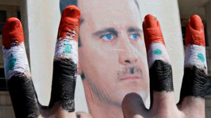 Two men with the fingers painted in the colours of the Syrian flag show the V-sign as they pose in front of a huge image of President Bashar al-Assad (AFP Photo / Anwar Amro)
