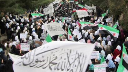 Demonstrators protesting against Syria's President Bashar al-Assad march through the streets in Homs December 13, 2011. (	