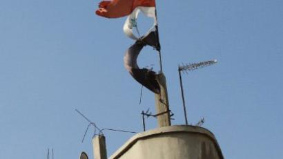 A picture taken on November 24, 2011 shows a torn Syrian flag fluttering on top of a building in the flashpoint city of Homs. (AFP Photo/Anwar Amro)