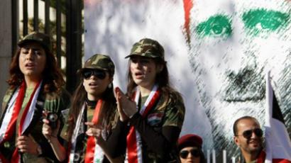Syrian pro-regime supporters dressed in military uniform stand in front of a mural of President Bashar al-Assad during a rally in Damascus on December 2, 2011 (AFP Photo / LOUAI BESHARA)
