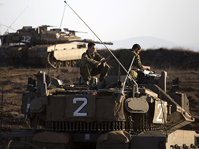 An Israeli Merkava tank crew sit on the Israeli annexed Golan Heights overlooking the Syrian village of Breqa on November, 06, 2012. (AFP Photo / Menahem Kahana)