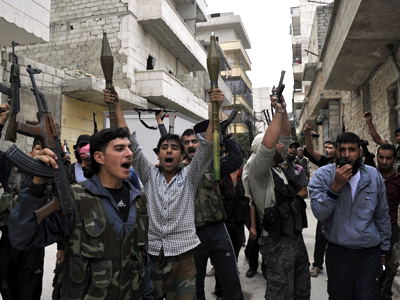 Syrian rebel fighters hold up their guns as they shout slogans in a street in the northern city of Aleppo (AFP Photo / Tauseef Mustafa)