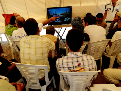 Syrian refugees watch news about their country on the United Arab Emirates' Orient News channel (AFP Photo / Mustafa Ozer)