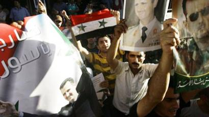 Syrians shout slogans as they demonstrate in support of President Bashar al-Assad (poster) in central Damascus (AFP Photo)